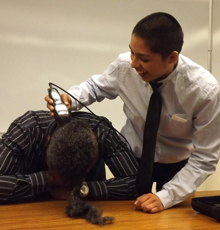 Social Science professor Milton Clarke gets shaved by Karen Hernandez.