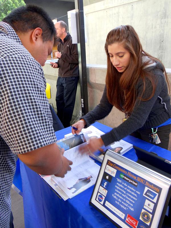 Guyllermo Santiago flips through a booklet for information on his Economics major with Transfer Admissions Specialist Melida Martinez representing San Jose State University during Transfer Day, Monday, Oct. 28.