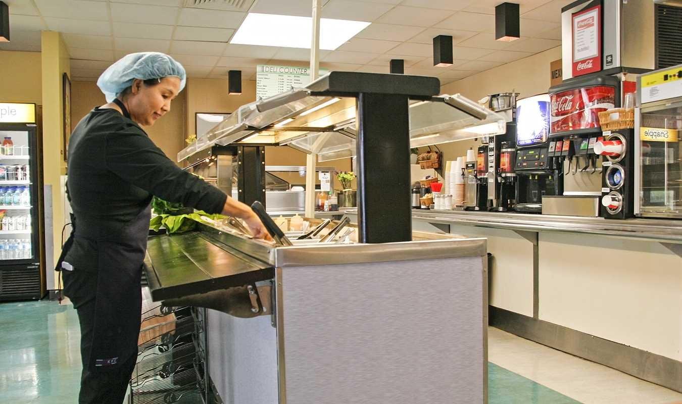Cafeteria Manager Jackee Kim from Fresh & Natural Corporation fixes up the salad bar. Photo by Cathie Lawrence.