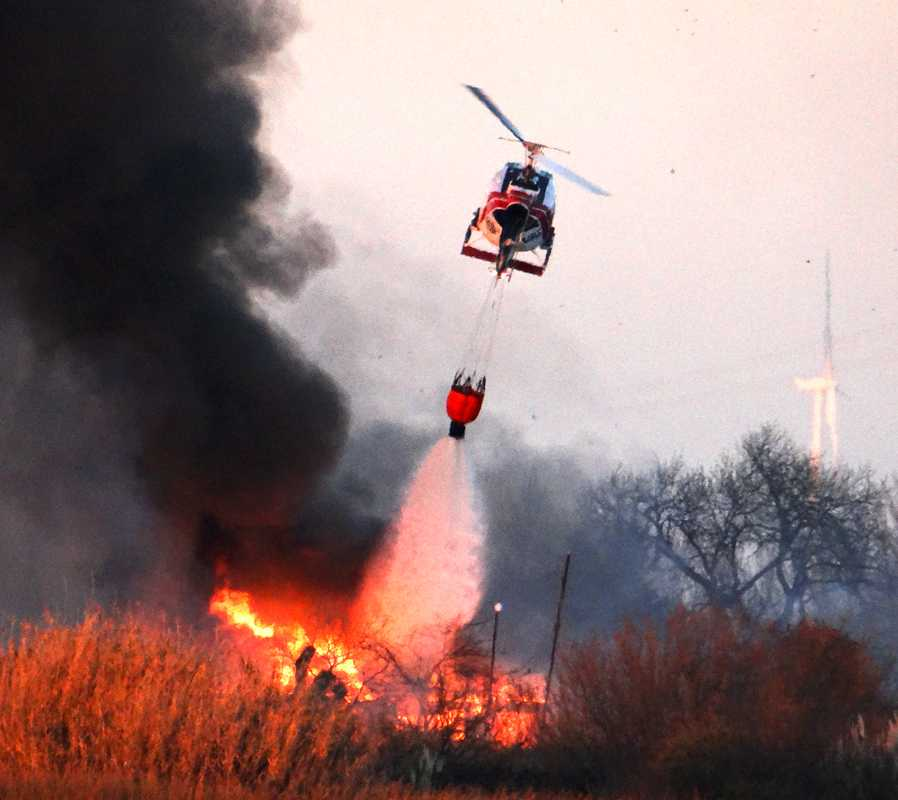 A+helicopter+drops+water+on+the+fire+to+extinguish+the+smoldering+fire.