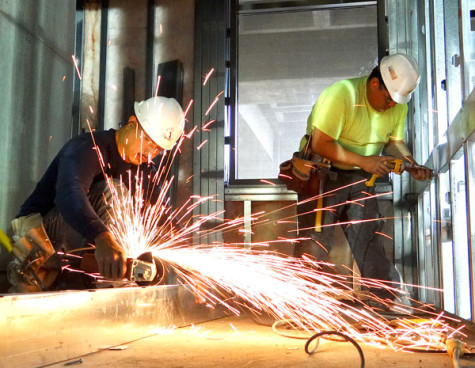 Sparks fly as Oscar Calvillo saws off a metal piece Feb. 12 inside the fourth floor construction zone that will be used for the proposed workroom in the Student Services building at the front of the College Complex.