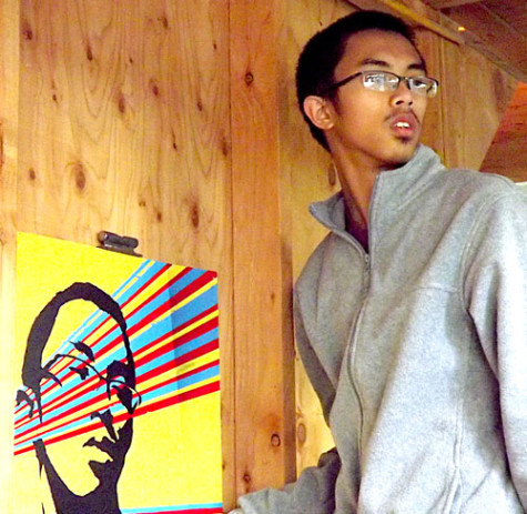 Ty Gocuan poses with his newly created art piece as it is being hung for display. He used a variety of colors and shades to construct his artwork. His piece was chosen as the Artist Statement Piece by members of his class. His portrait is on display with others on Level 3 of the College Complex.