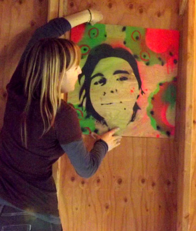 Professor Judy Pettite works with students to display student Sydnie Sherman's self-portrait before spring break.