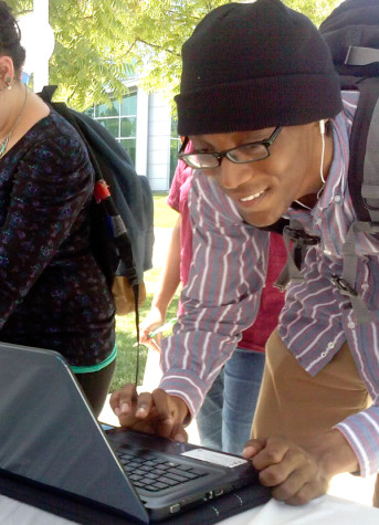 Student Malik Lawson casts his vote on one of the laptops provided. The voting was held in the outdoor quad. Voters received a free lunch for their participation.