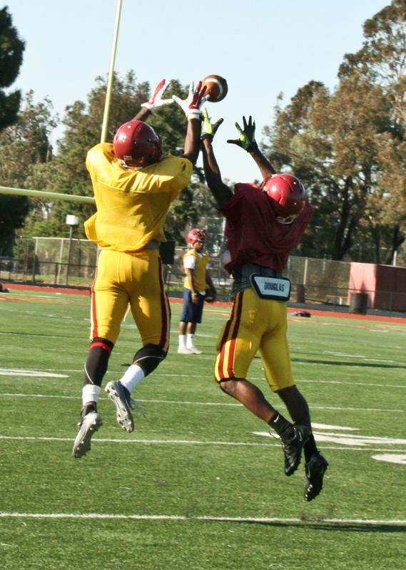 During Mustangs football practice, wide receiver Alejandro Phillips (left) jumps for the pass as defensive back Jamon Ward (right) leaps to break up the play.