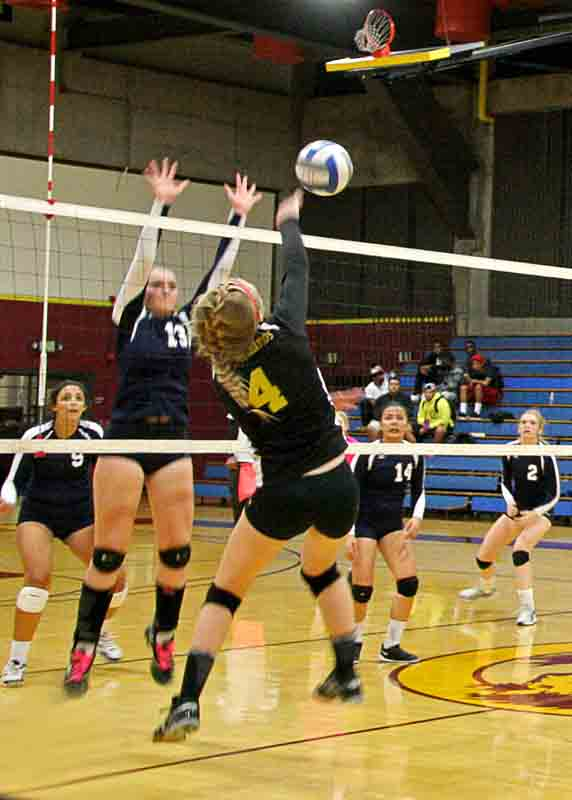 LMC+outside+hitter+Lindsay+Baynes+leaps+to+hit+the+ball+around+Yuba+middle+hitter+Shon+Ritchie.+
