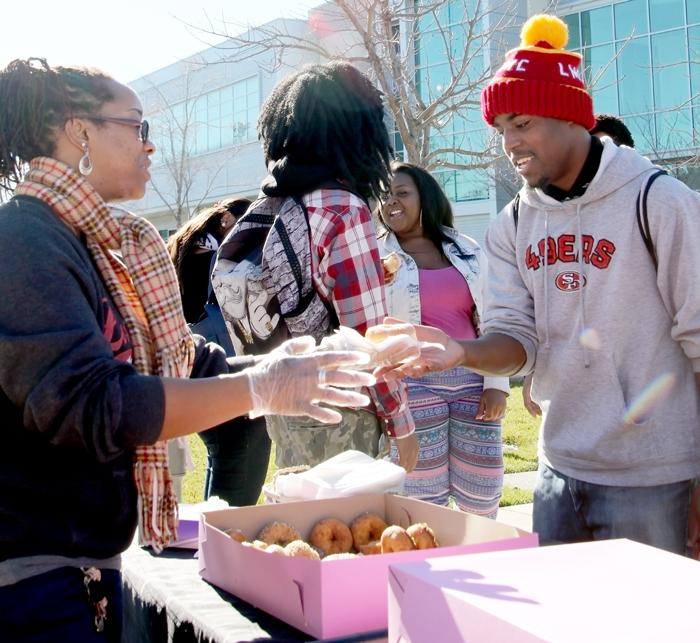 Student Life coordinator Demetria Lawrence treats student Eddie Coats during Mustang Day.