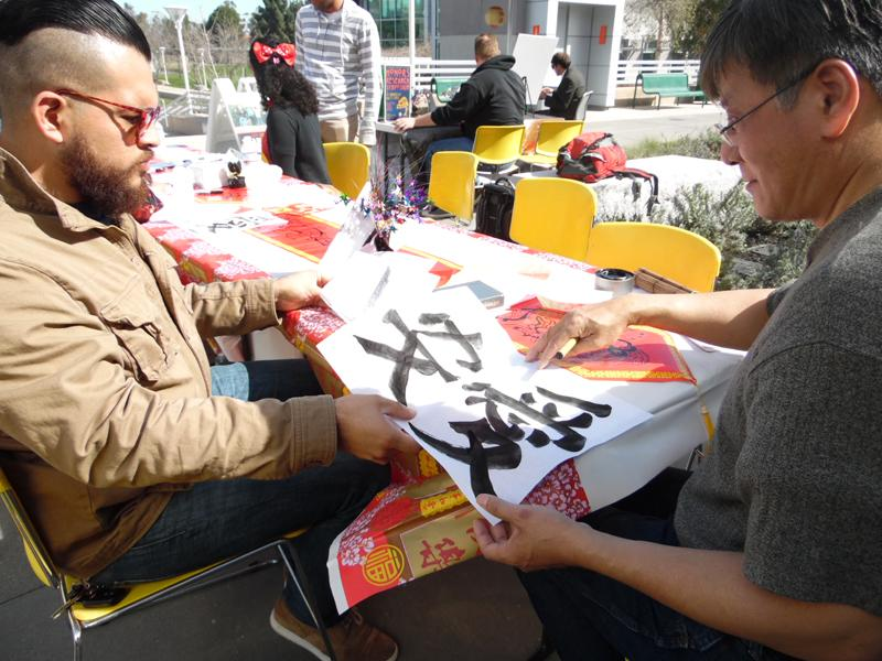 Artist Dave Fung and student Kenny Purizaga draw peace and love at the calligraphy workshop,