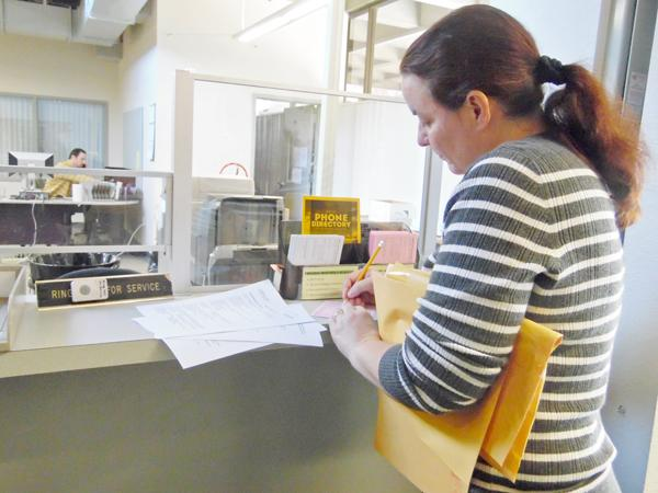 Instructional Assistant Jennifer Garcia fills out a request form at the new temporary location of the print shop.