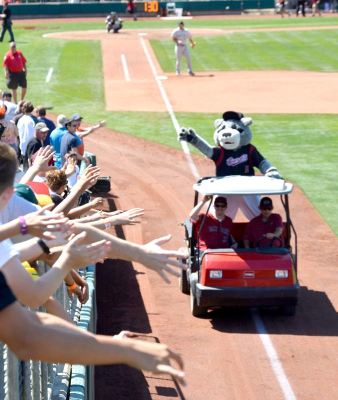 Fans reach out for Sacramento Rivercats mascot Dinger as he rolls around the park delivering gifts and collectibles in between innings.