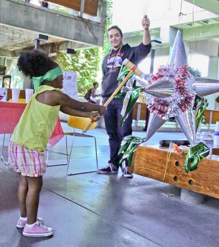 Imani Grigsby, daughter of an LMC student hits a pinata held by Club LEO President Collin Brown at the Cinco de Mayo event in the indoor quad.