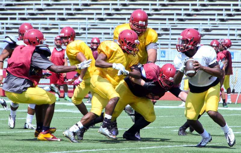 Defensive back Rayshaun Hicks, left, and lineman Eddie Yanes, back, try and defend against quarterback Julius Mozee, right, as he rolls out of the pocket during an Aug. 15 practice.