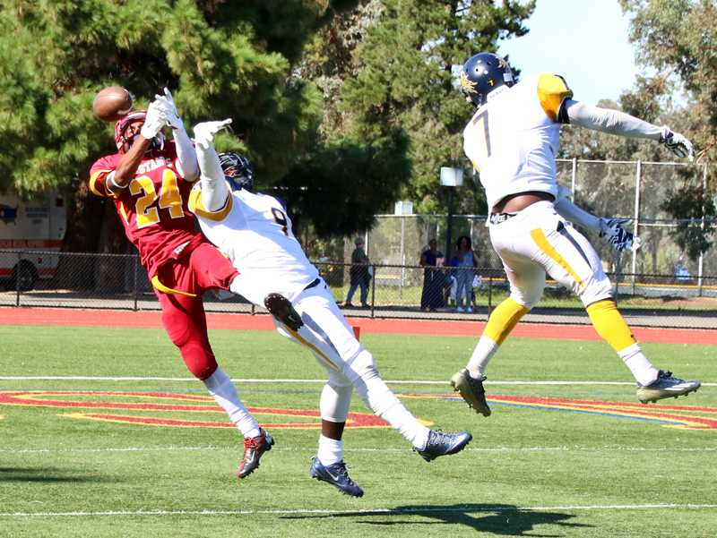 LMC wide receiver Lymond Glover-Walker goes up to catch a 4th down pass toward the end of the game as Merced defensive backs Tazarium Thomas and Demario Guyton (right) defend the play.
