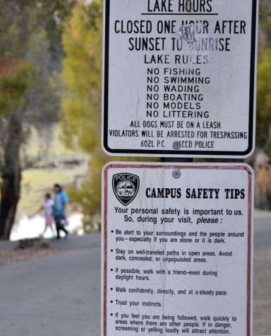 Signs posted by the entrance to the lake sate rules and campus safety tips for students and staff.