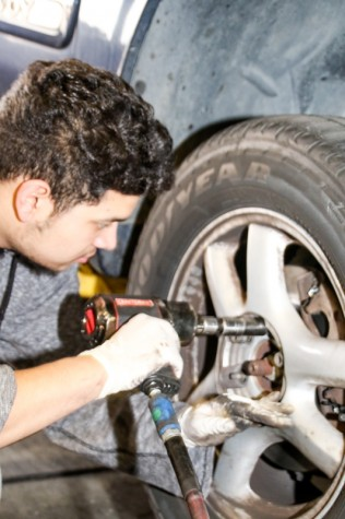 LMC Automotive, December 2, 2015. Brake day is wednesday at LMC, Rene Ayala is putting lug nuts back on to the tire. Cathie Lawrence/Experience.