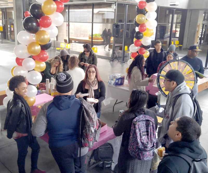 Student Life Coordinator Melina Rodriguez hands out  doughnuts at a warm-up event Monday Jan. 25