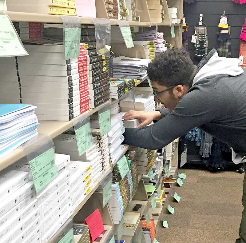 LMC+Bookstore+employee+Nick+Murphy+sorts+through+the+diverse+selection+of+English+100+textbooks.%0A+