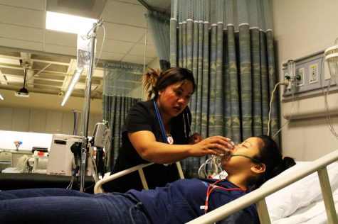 Melissa Cardenas gives a patient oxygen in the hospital area after the explosionh
