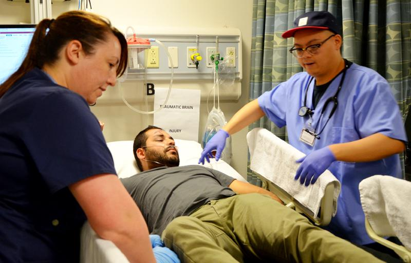 Hassib Falez is treated by Laura Campbell (left) and Michael Mungcal (right) after suffering a simulated traumatic brain injury Wednesday, May 4.