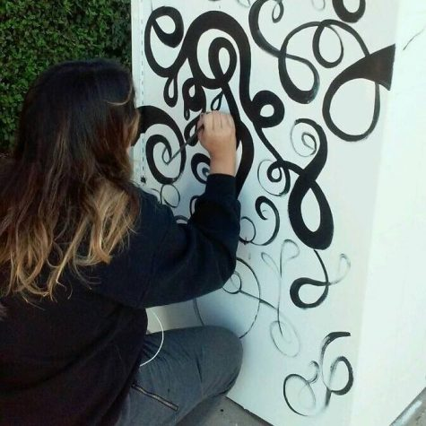 Gomez painting the side of her utility box.