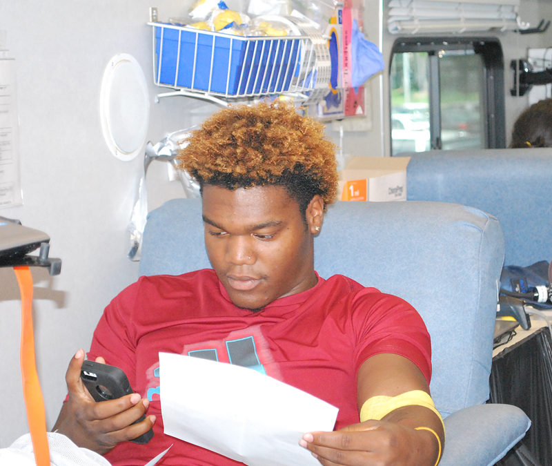 Armani+Smith+reclines+in+the+blood+bus+as+he+donates.+