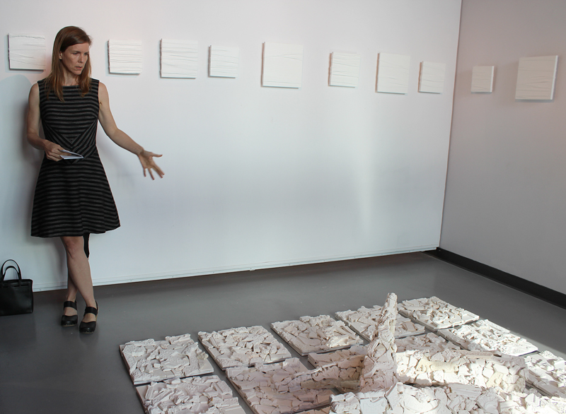 "Artist Karrie Hovey gestures at her art piece ""[Trans]act"" which focuses on rhino horns."
