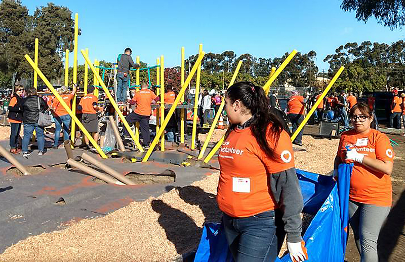 Volunteers lift materials and hold up poles during the playground's construction.