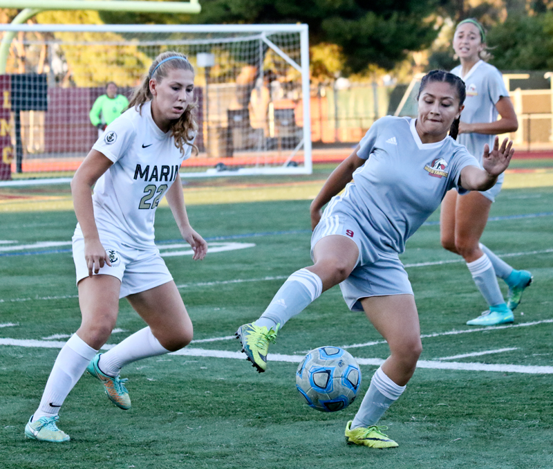 LMC Women Soccer vs. Marin College. LMC player #9 Adriana Urrutia sweeps backl away from Marin Playeer #22. Disa Johannson. October 27, 2017. Los Medanos College, Pittsburg, Ca.