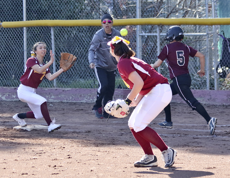 Mary Borlongan attempts to record an out reaching for the ball thrown by captain Brittany Bangert.