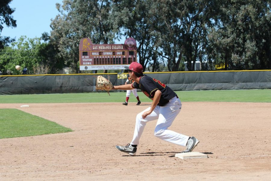 LMC first baseman (#22) Vince Lontz catches ball before Solano player makes it to base. LMC played  their second game against Solano College and won. On April 14, 2018. Los Medanos College, Pittsburg, Ca.