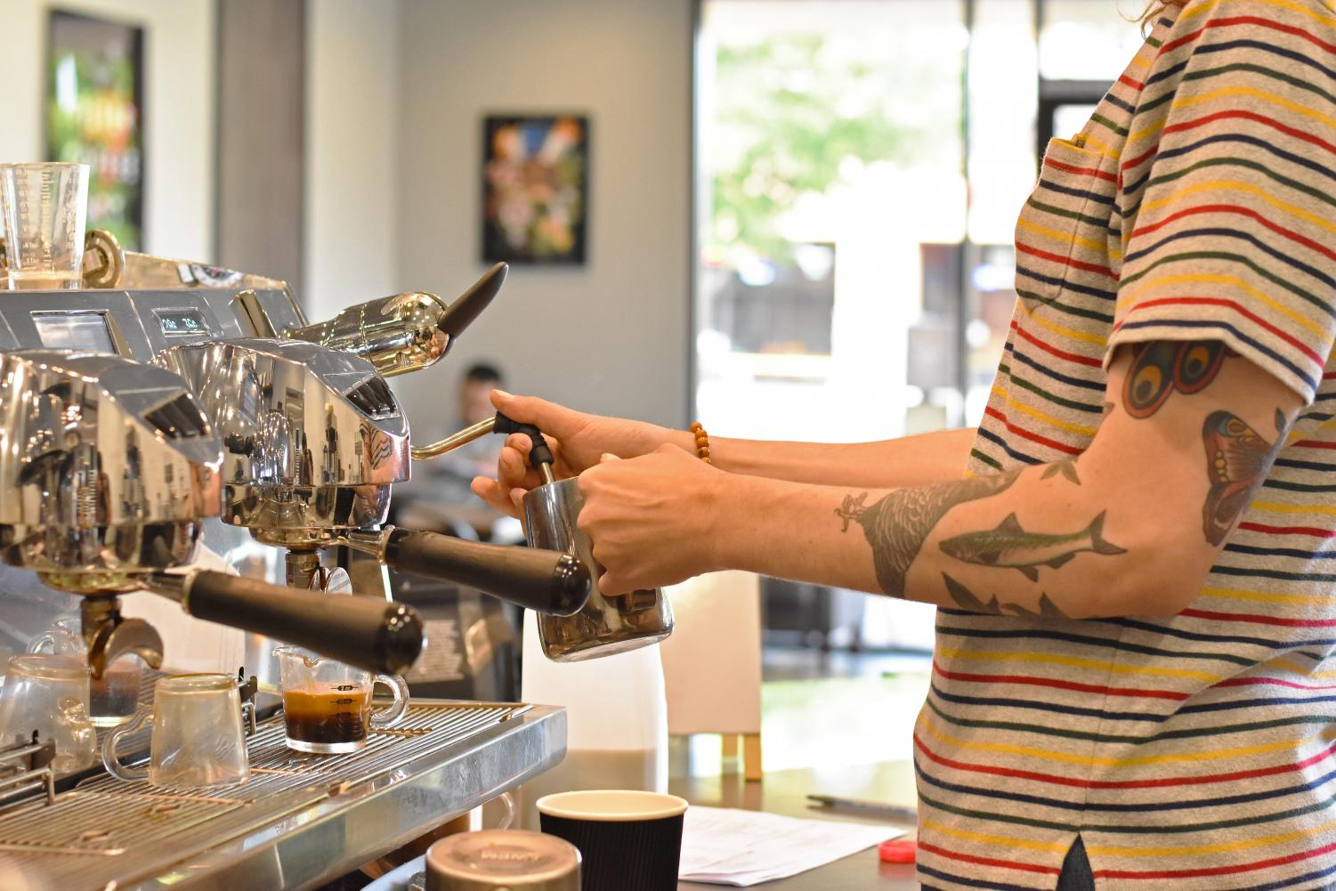Barista steams a latte behind the counter at Big House beans.