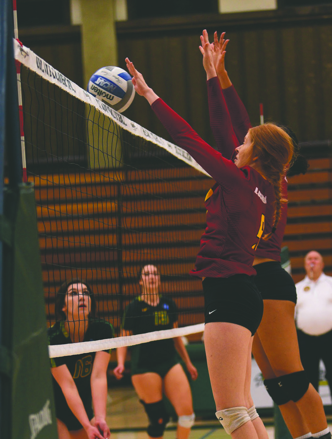 Emily Sobolik blocks the ball from entering her side of the court.