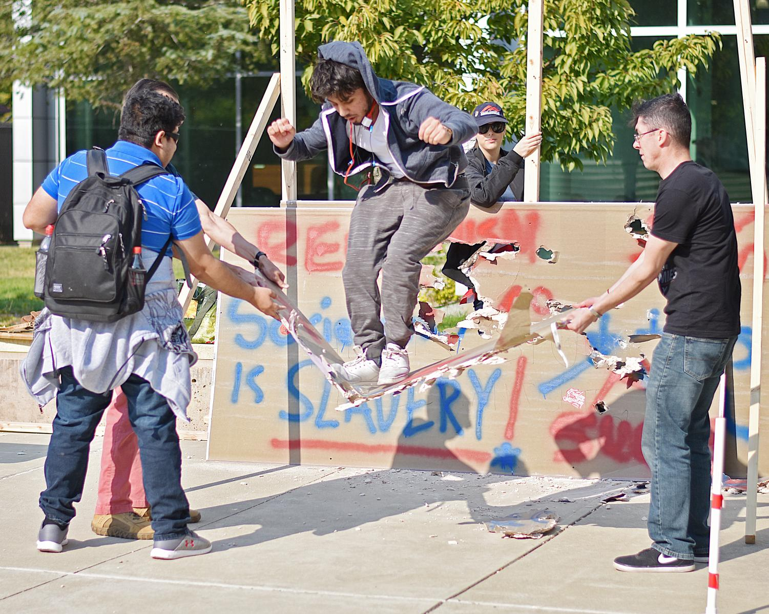 Aadil Faith smashes through a segment of Young American's for Freedom's 'Berlin Wall.'