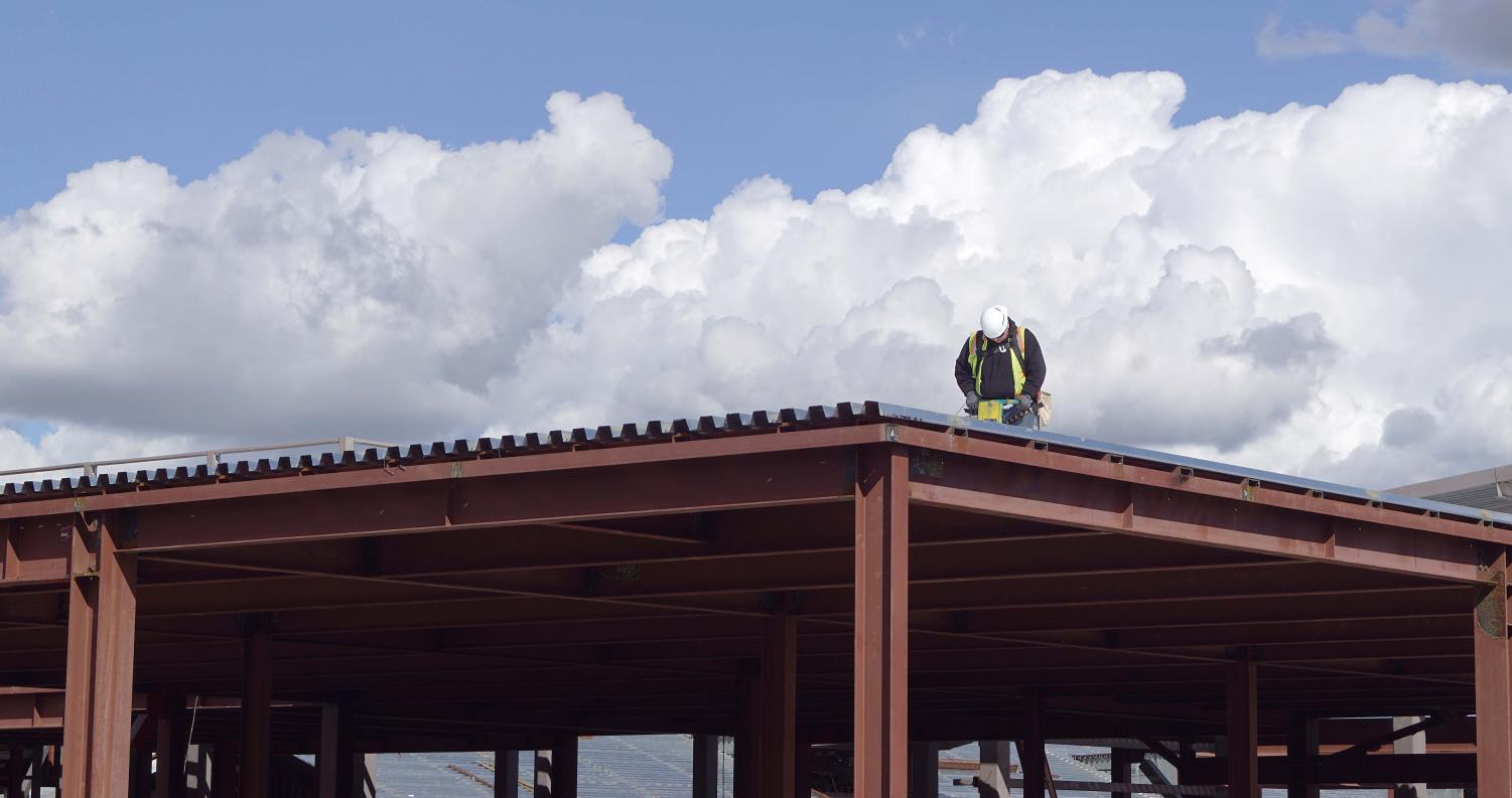 A construction worker stands atop the roof of the new campus building as he works on the framework of the building.