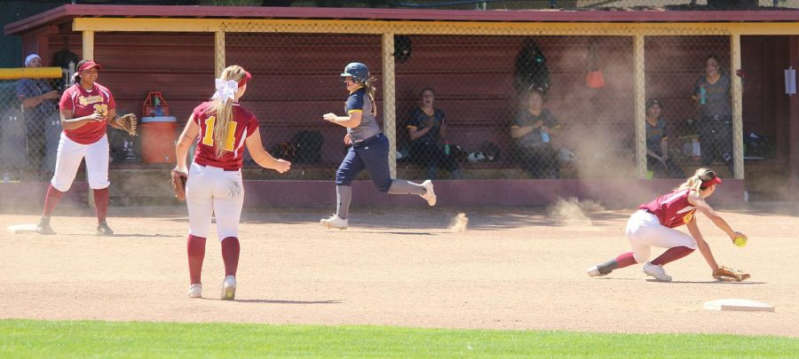 Pitcher Mary Borlongan fields a ball but is unsuccessful in recording the out.