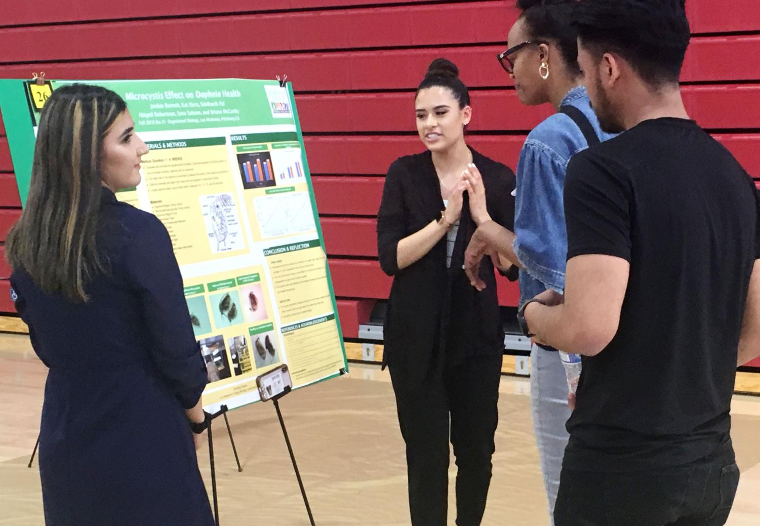 Sana Saleem (left) and Kat Elera present their poster about research on Daphnia to students.