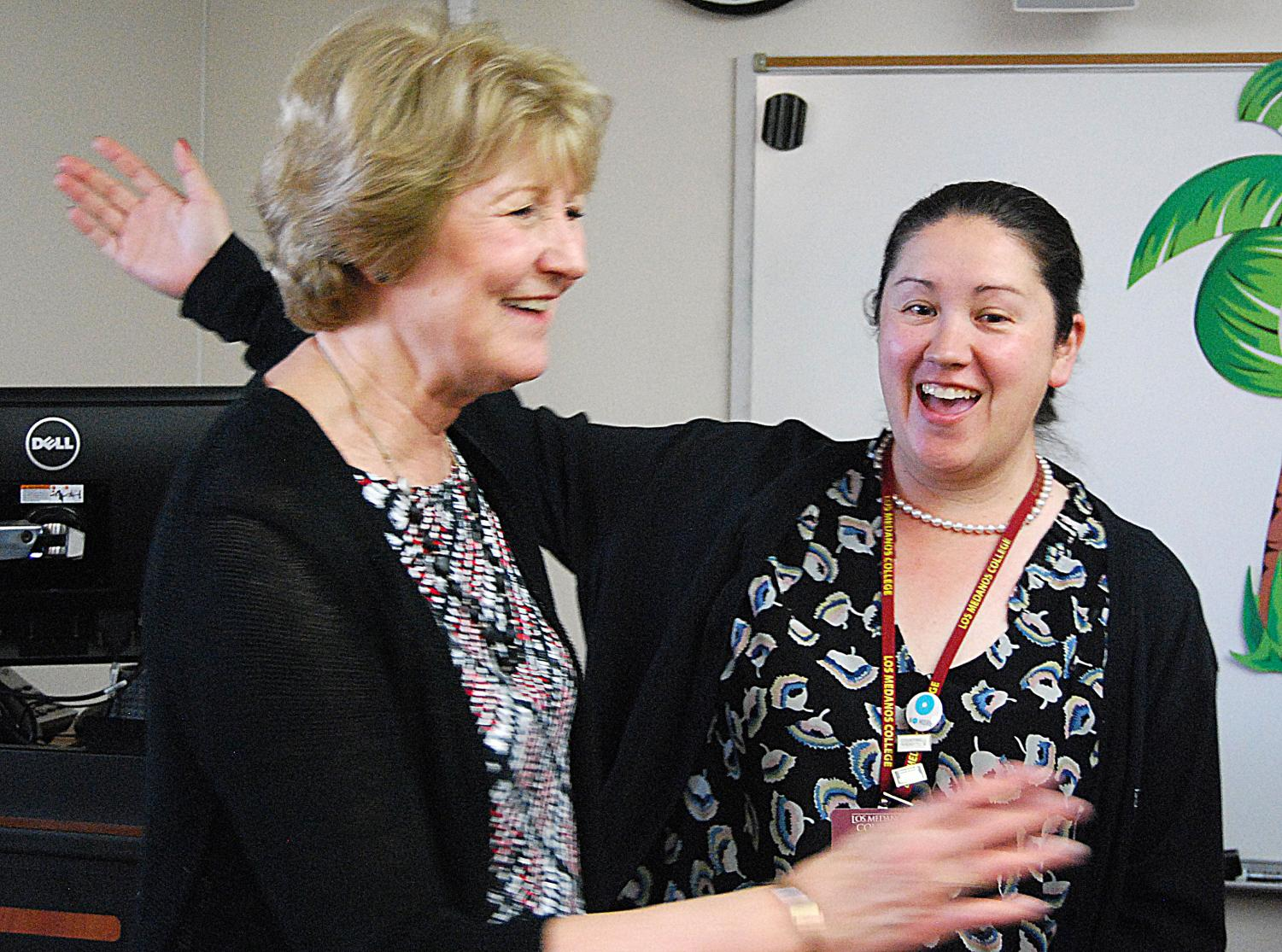 Financial aid assistant Deborah Baskin goes in to hug Gail Newman at the vp's retirement party.
