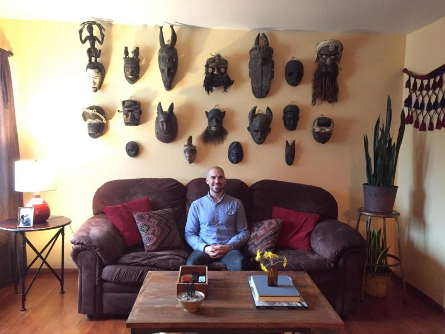 Zack Feere at his home in Antioch, sitting on his couch in front of his African art collection.