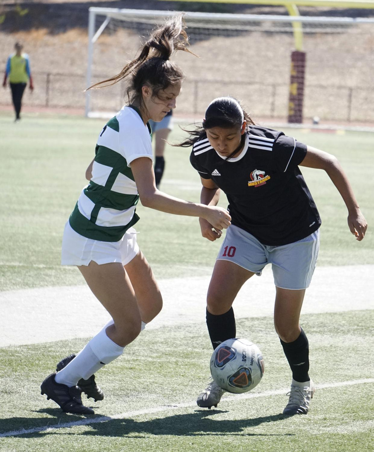 Litzy Rodriguez, No. 10, battles against a Cañada College defender for the ball. during a soccer game on Sept. 13.