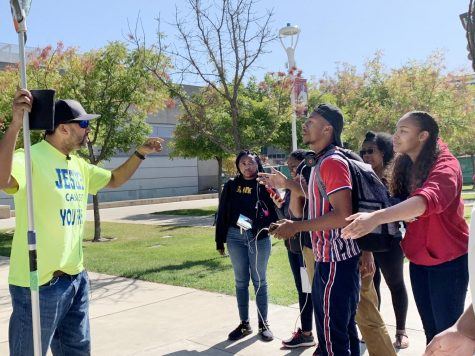 "Student Arron Homes argues with a man in a ""Jesus can set you free"" T-shirt who walked onto campus Thursday to proselytize. Many other students also gathered around in the outdoor quad to challenge his religious perspectives."