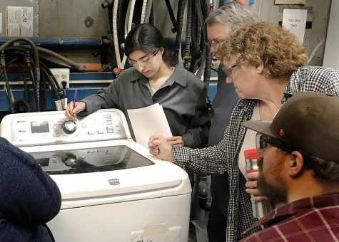 Student Marlene Lopez (left), Steve Lowery and Instructor Debra Winckler go over how to fix a washer.