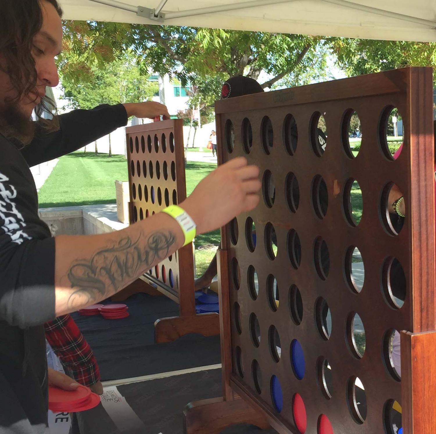 Los Medanos College student Chris Melgar tries his luck playing on a giant Connect Four game board made of wood at the EOPS 50th anniversary celebration Tuesday, Oct. 1.
