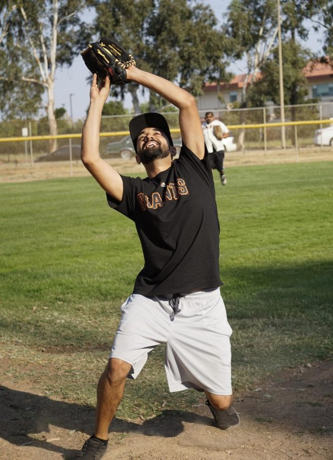 Staff member Erwin Cadena catches the ball during the staff softball game.