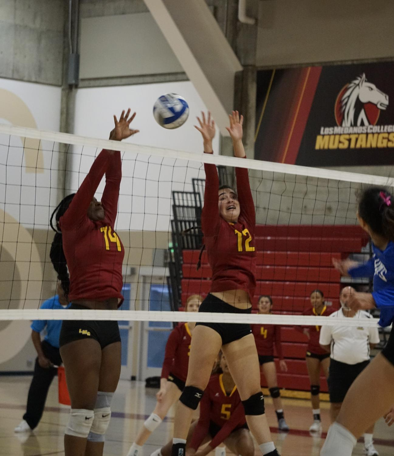 Jazlyn Avelino, No. 14, and Sophia Corini, No. 12, block the ball.