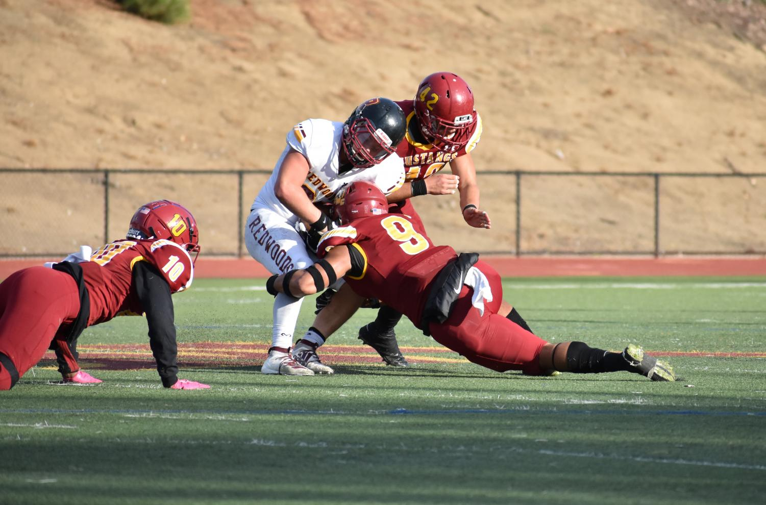 Line backer Heamasi Latu, No. 9, makes a tackle on a player from College of the Redwoods.