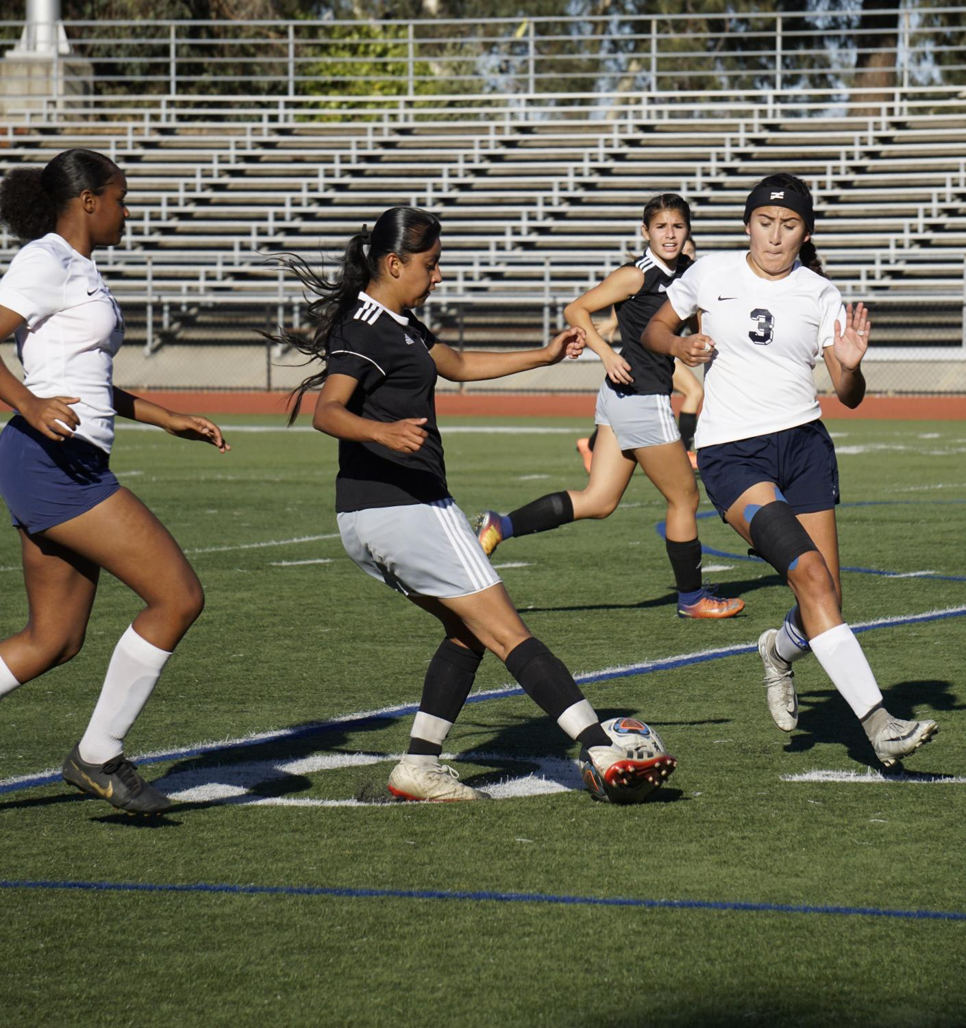 Litzy Ramirez, No. 10, dribbles around two defenders and makes a pass to Anissa Gomez, No. 12.