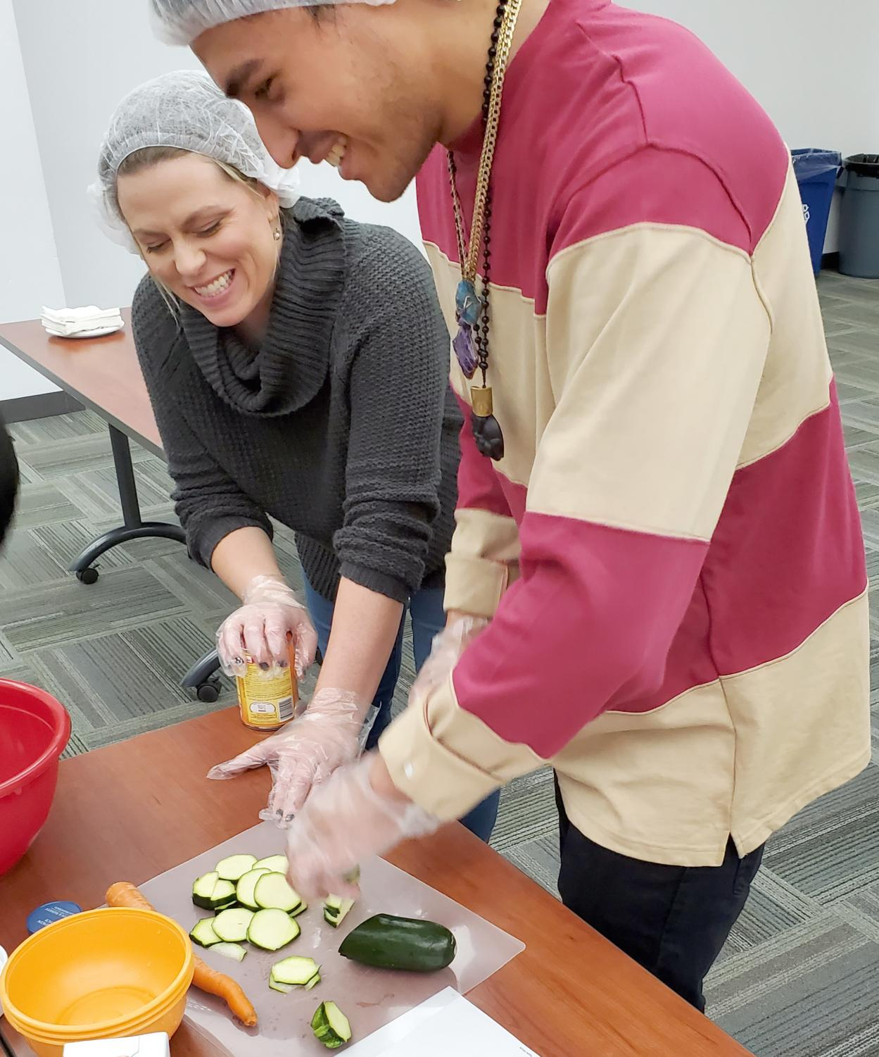 Renee Savage and Manny Jimenez prepping vegetables for corn and green chili salad.