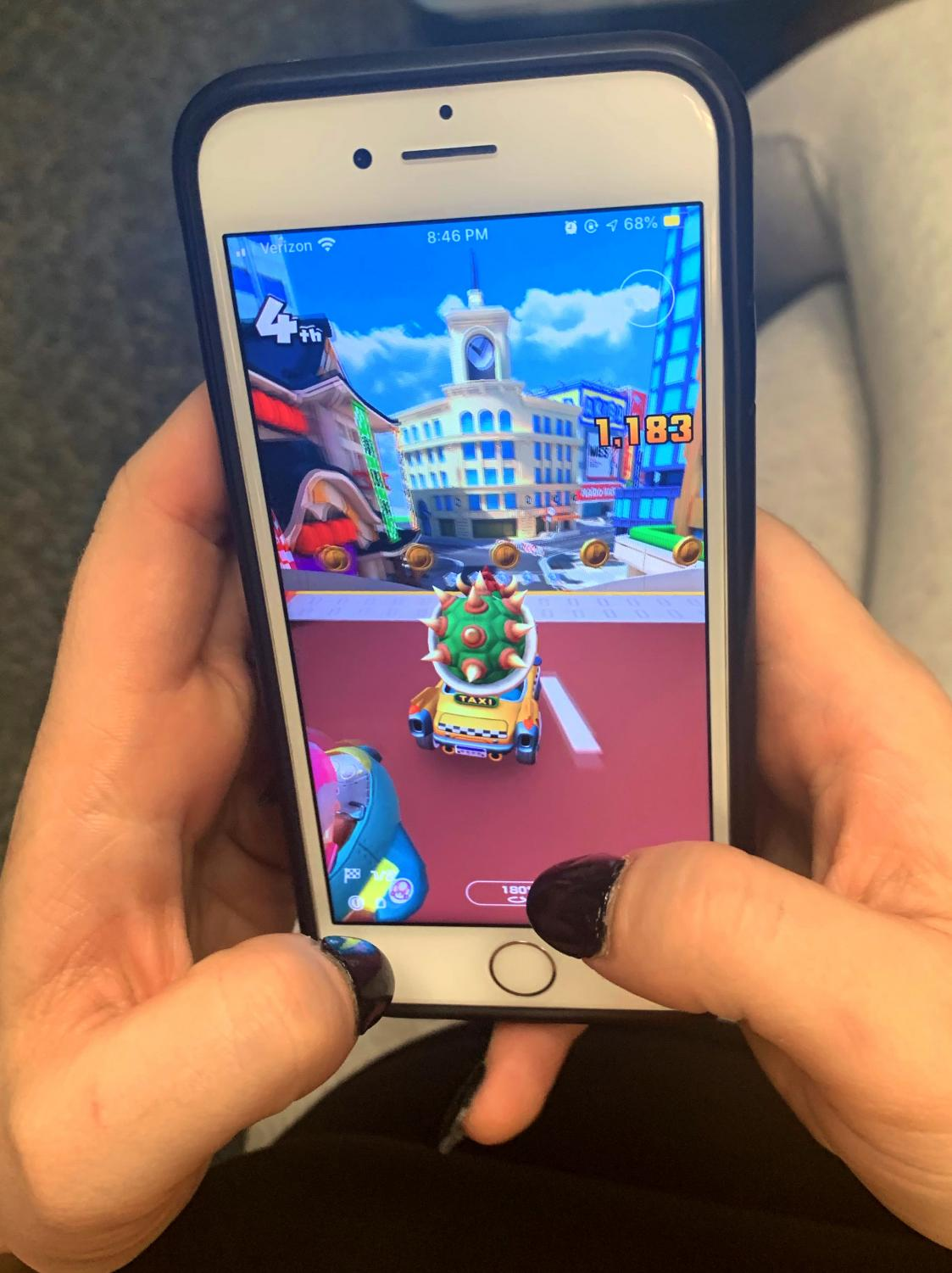 Gamer plays Mario Kart Tour on iPhone, tilting phone and using fingers to control the racing avatar with precision.