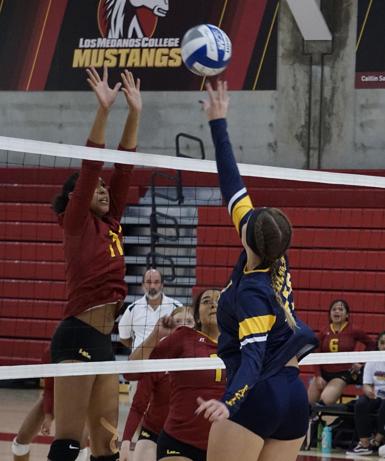 Amaya Mixon, No. 11, jumps above the net to block the ball from going over the net against a Mendocino College player.