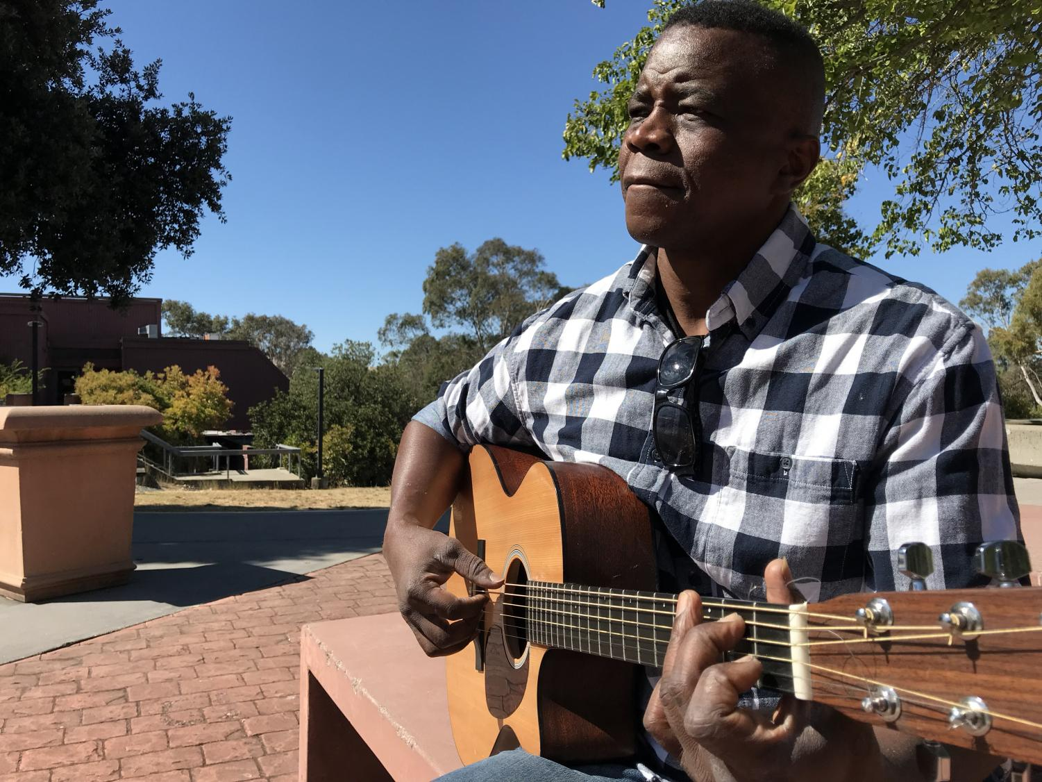 LMC student and musician Bona Nsiala plays guitar on campus for passersby to listen to.